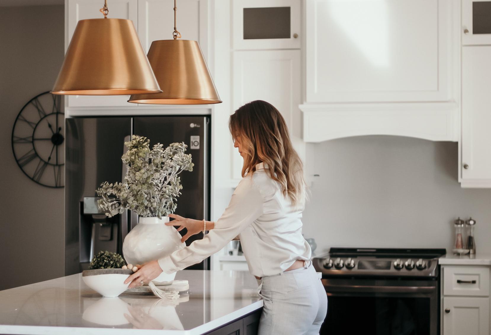 Christine adjusting a vase in kitchen