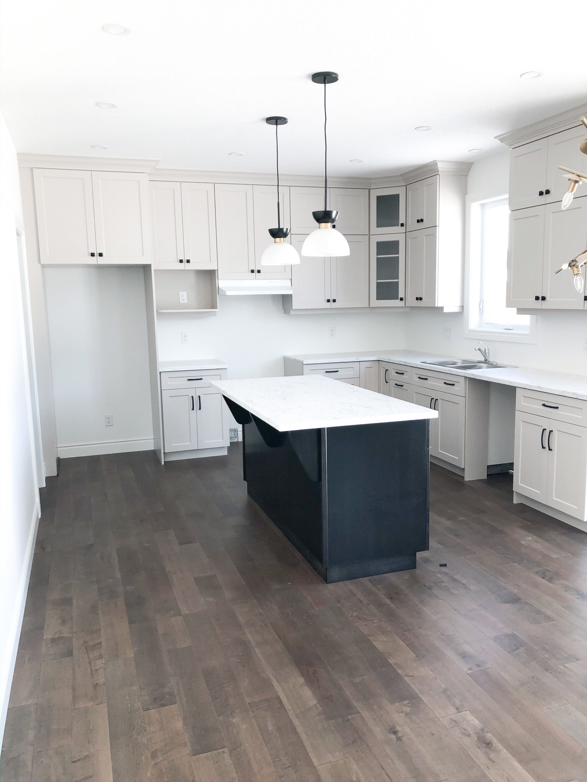 overview of kitchen featuring white cabinets, black island and modern pendant lighting