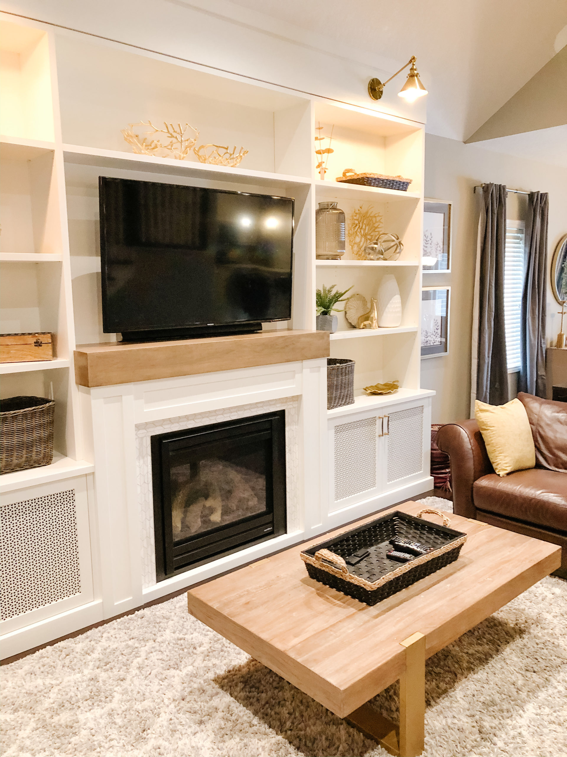updated all white built in gas fire place and stylized shelving with tv and mantle