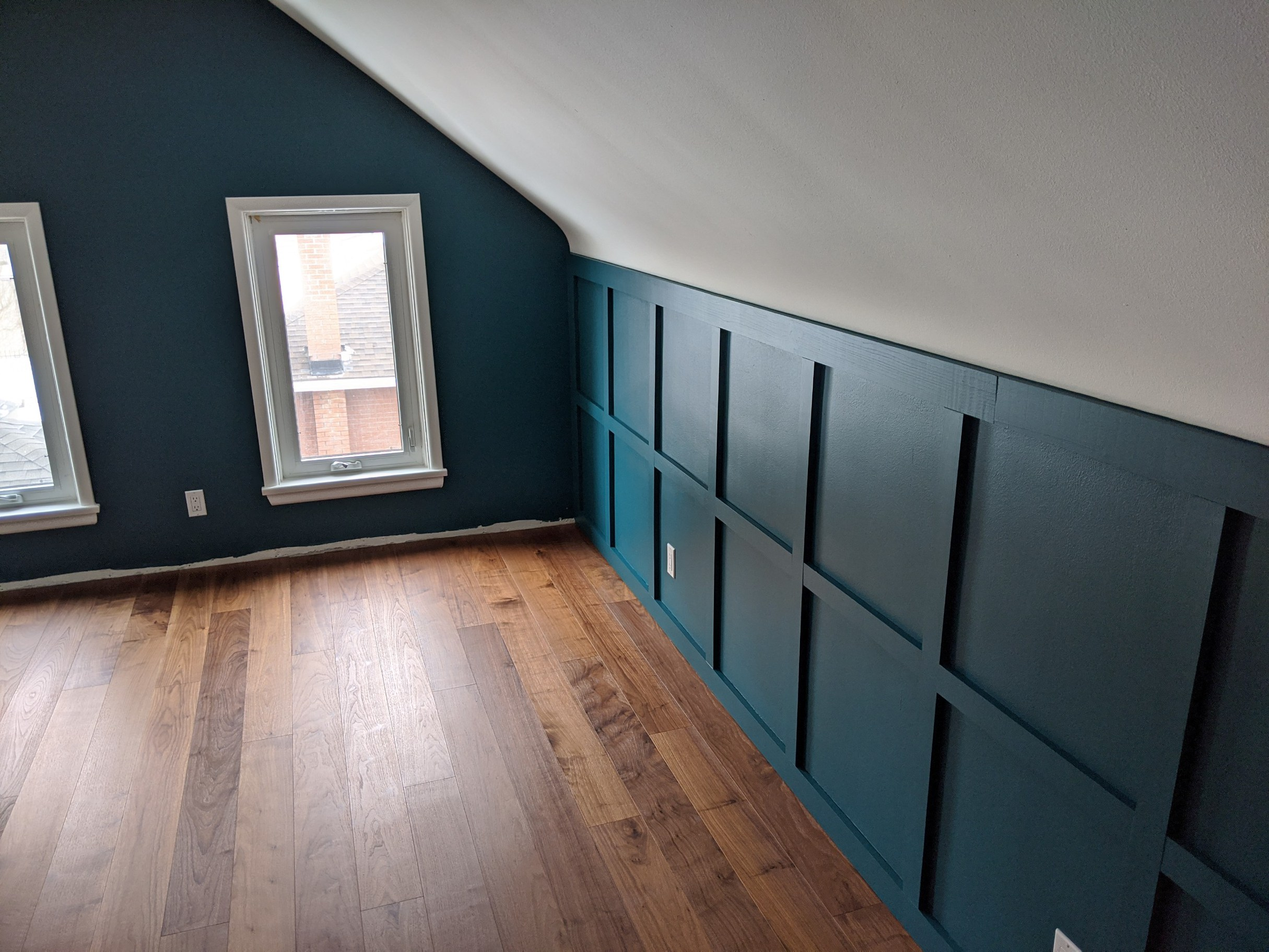 angled ceilings, teal painted walls and hardwood floor