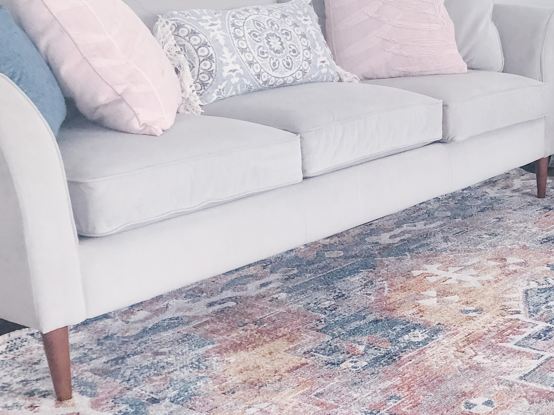 light couch with pastel pillows on top of a pastel printed rug