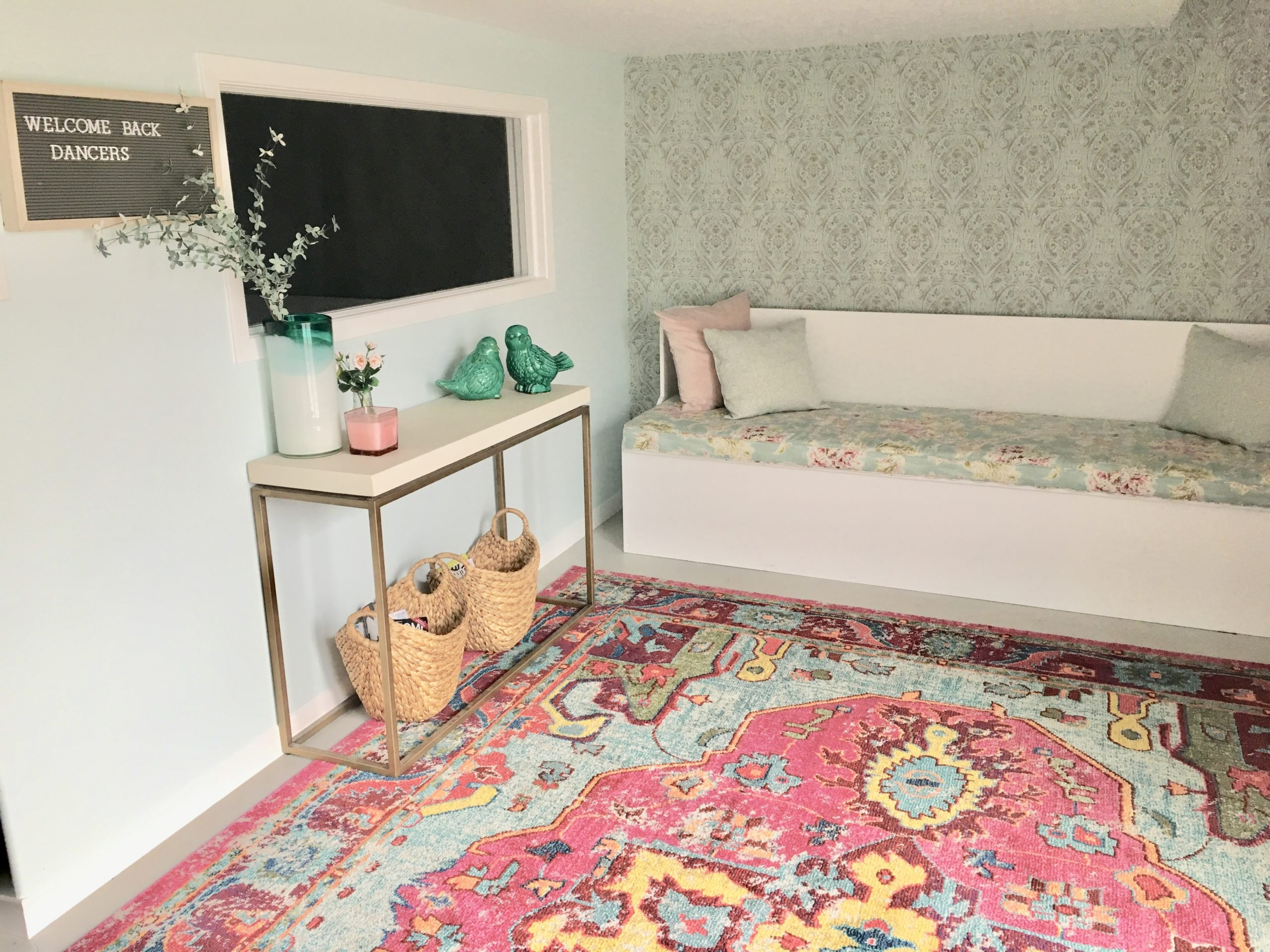 dance studio change room featuring built in bench and ornate rug
