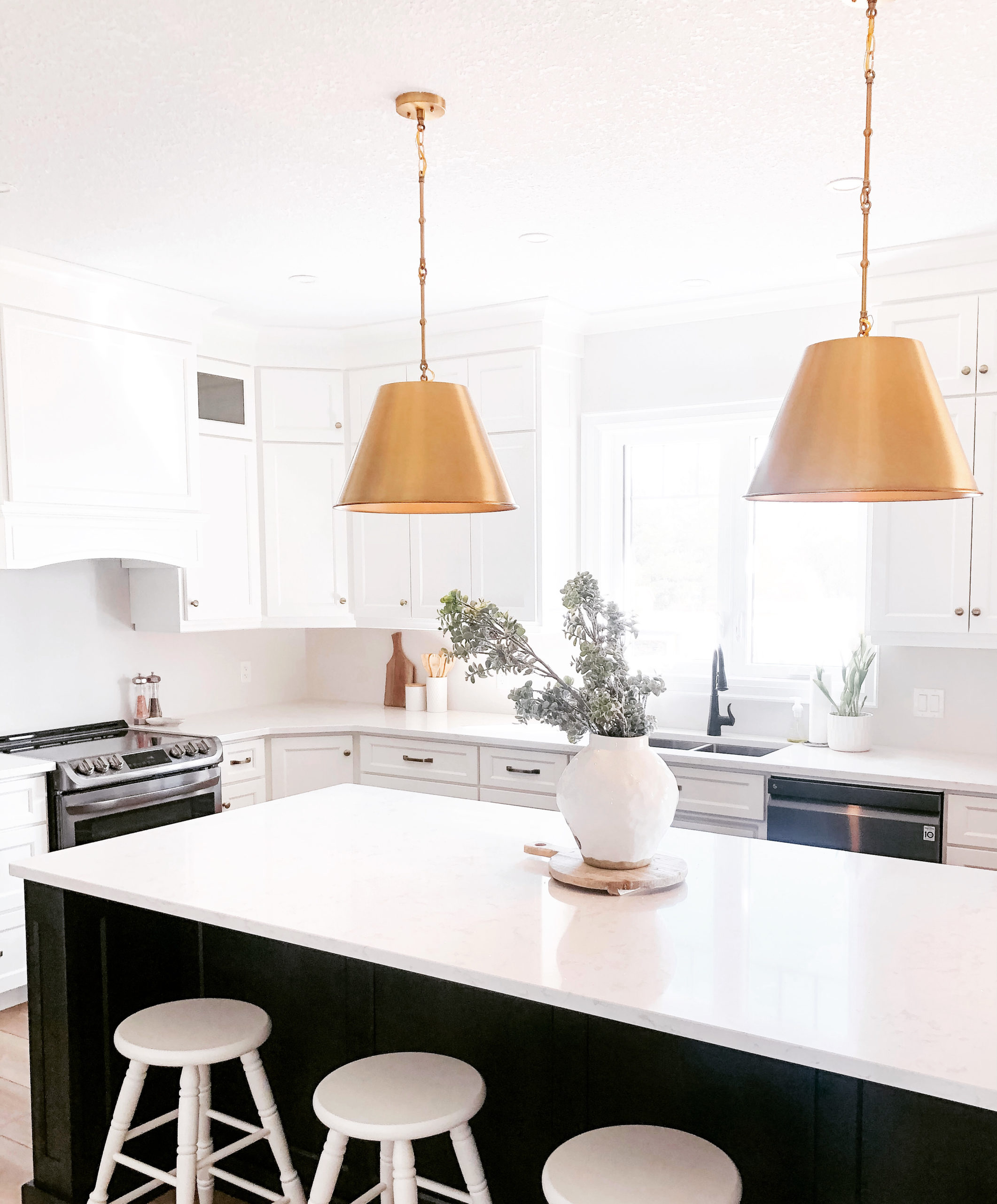 kitchen overview featuring gold pendant lights, white bar stools and white overhead range