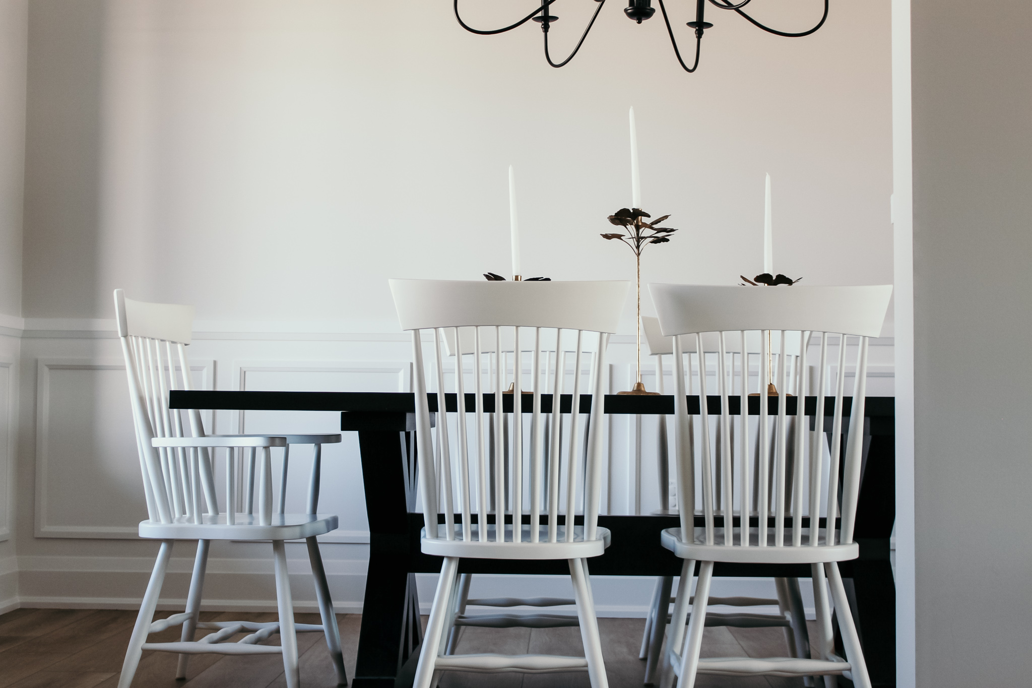 black kitchen table with wood painted white chairs and black iron light fixture